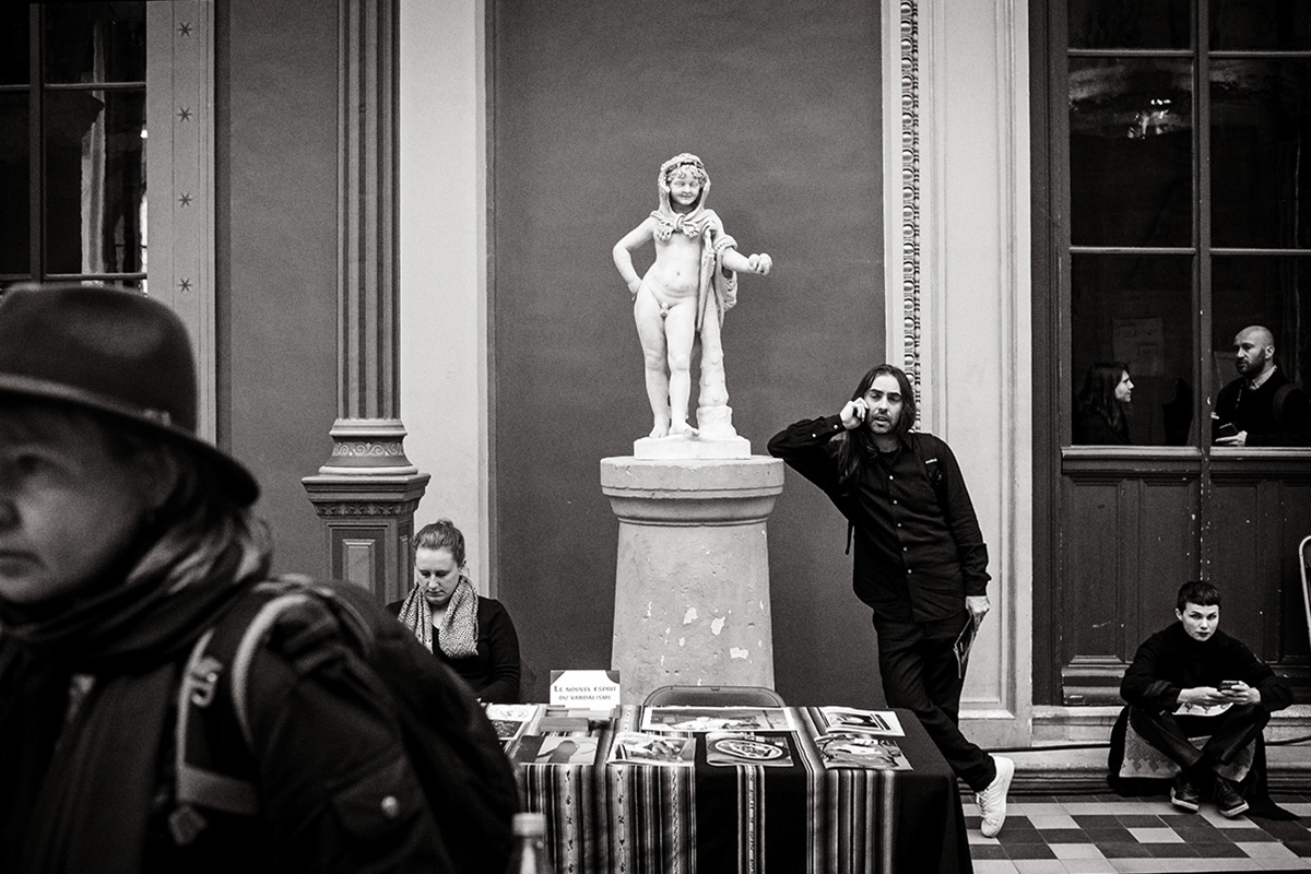Man leaning against statue at Offprint book fair, school of Beaux Arts, Paris